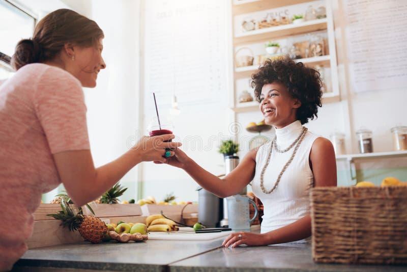 Kvinnlig bartender som tjänar som ett exponeringsglas av ny fruktsaft till kunden royaltyfri fotografi