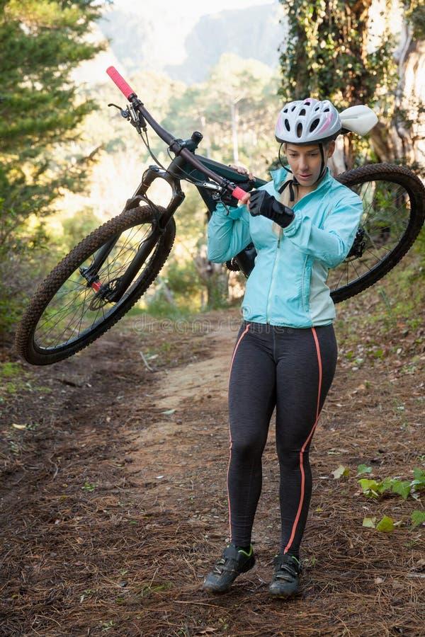 Kvinnlig bergcyklist som bär hennes cykel i skogen royaltyfria foton