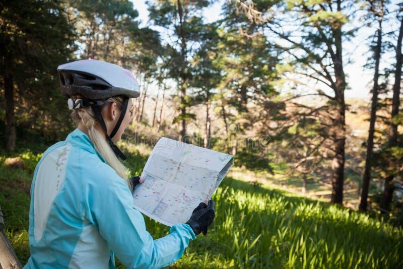 Kvinnlig bergcyklist som ser översikten arkivfoton