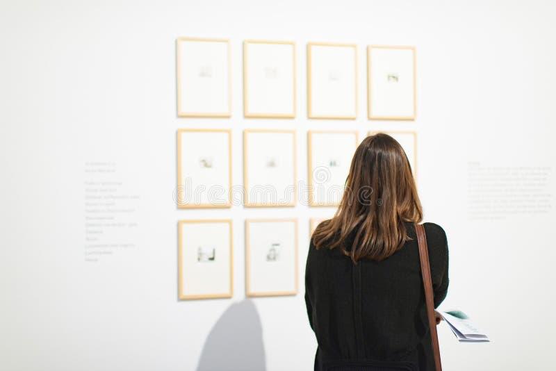 Kvinnlig besökare som ser konstverk på den vita väggen i museumrum arkivfoto