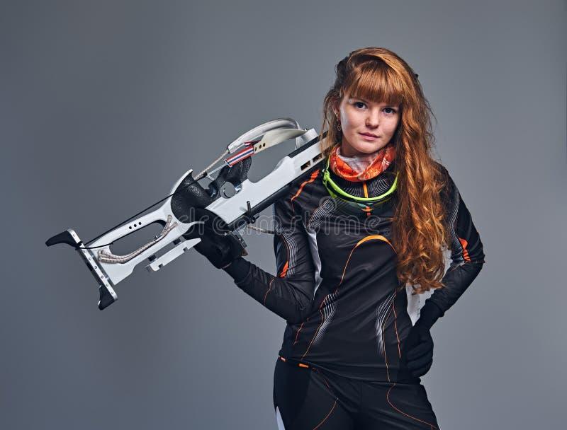 Kvinnlig Biathlonm?stare f?r r?dh?rig man som siktar med ett konkurrenskraftigt vapen arkivfoto