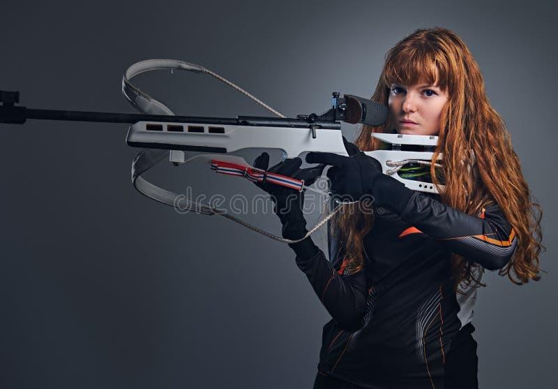 Kvinnlig Biathlonm?stare f?r r?dh?rig man som siktar med ett konkurrenskraftigt vapen arkivbild