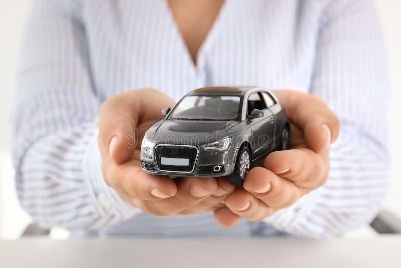Kvinnlig bil för leksak för innehav för försäkringmedel fotografering för bildbyråer