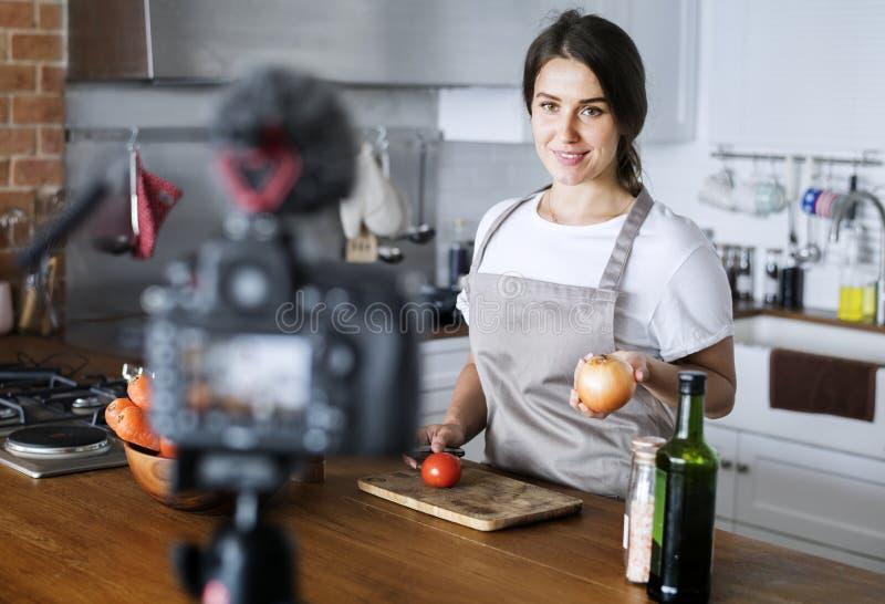 Kvinnlig bloggerinspelning som hemma lagar mat släkt TV-sändning royaltyfri bild
