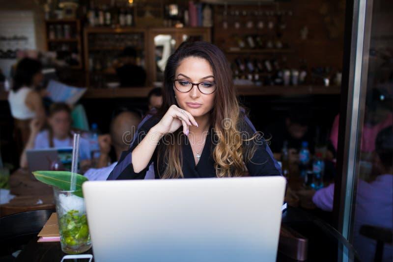 Kvinnlig bloggerläsningartikel i internet via anteckningsboken under fri tid i restaurang fotografering för bildbyråer