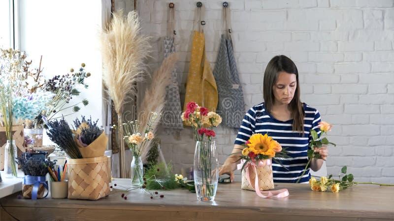 Kvinnlig blomsterhandlare i blomsterhandel på arbete arkivbild