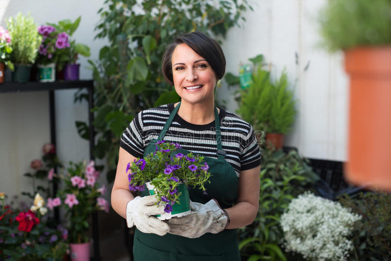 Kvinnlig blomsterhandlare i det arbeta i trädgården lagret royaltyfri foto