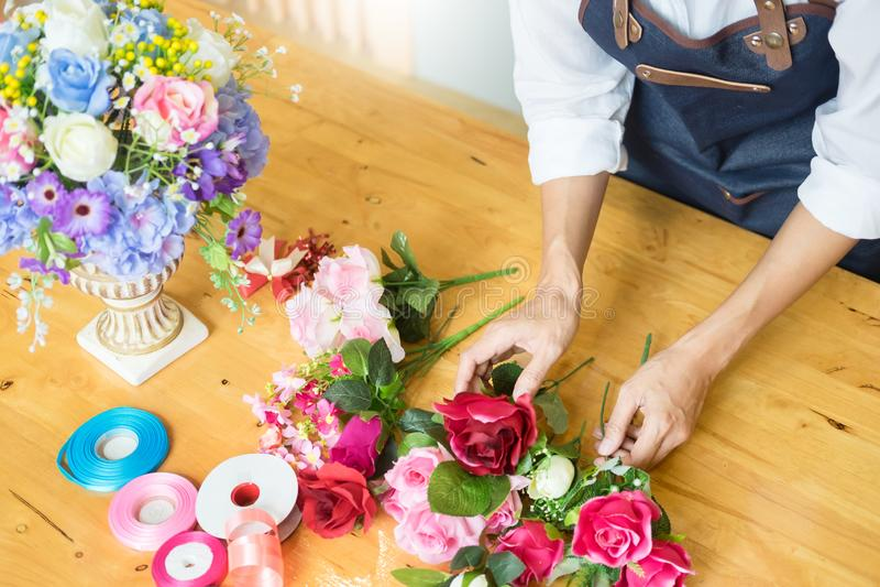Kvinnlig blomsterhandlare på arbete genom att använda att ordna göra härliga Artifici arkivbilder