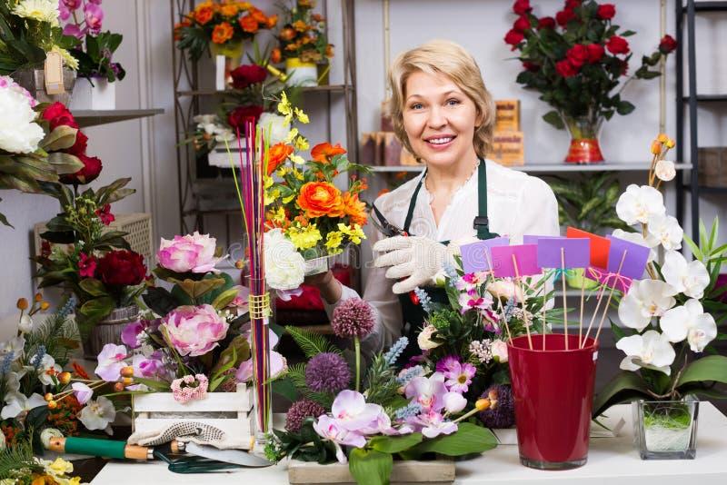 Kvinnlig blomsterhandlare på arbetet royaltyfria bilder
