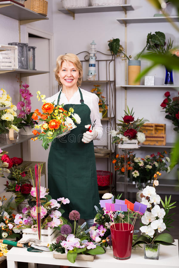 Kvinnlig blomsterhandlare på arbetet arkivfoto