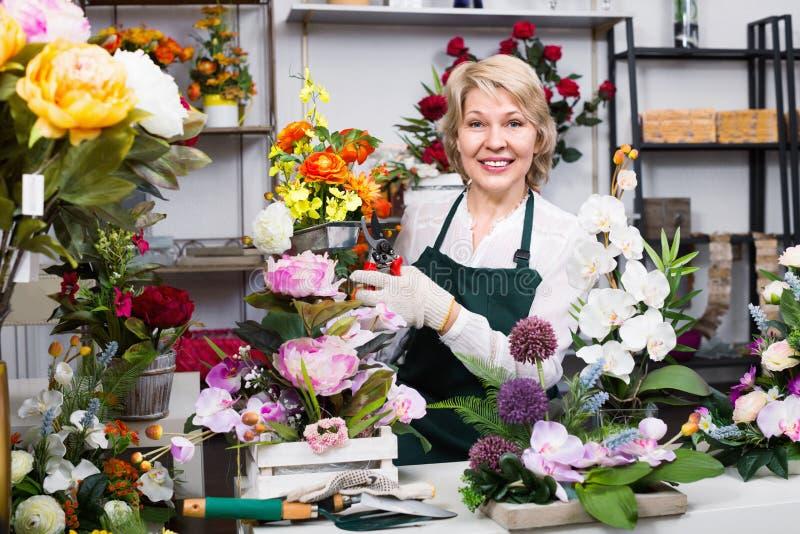 Kvinnlig blomsterhandlare som bär ett förkläde och förbereder lyckligt blommor arkivfoto