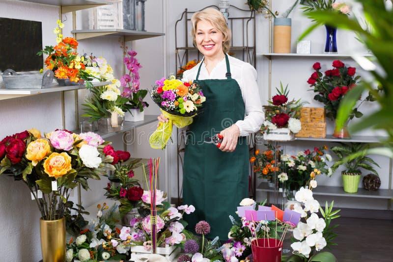 Kvinnlig blomsterhandlare som bär ett förkläde och förbereder lyckligt blommor arkivbilder