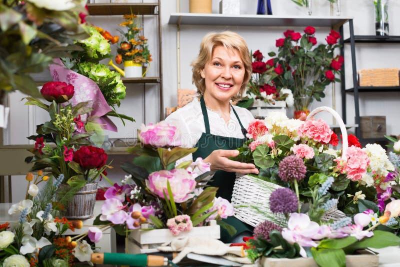 Kvinnlig blomsterhandlare som bär ett förkläde och står lyckligt bland flowe arkivfoton