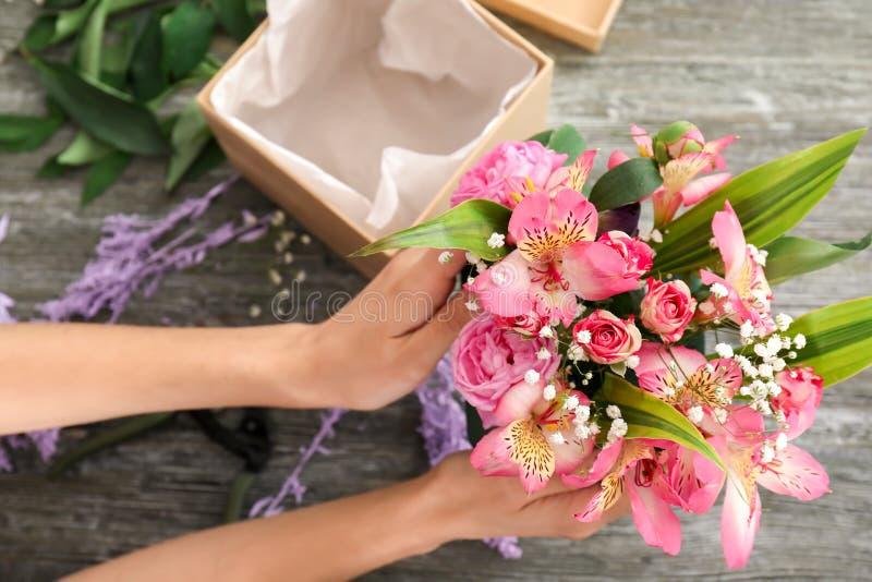 Kvinnlig blomsterhandlare som förbereder asken med härliga blommor på tabellen, closeup royaltyfri fotografi