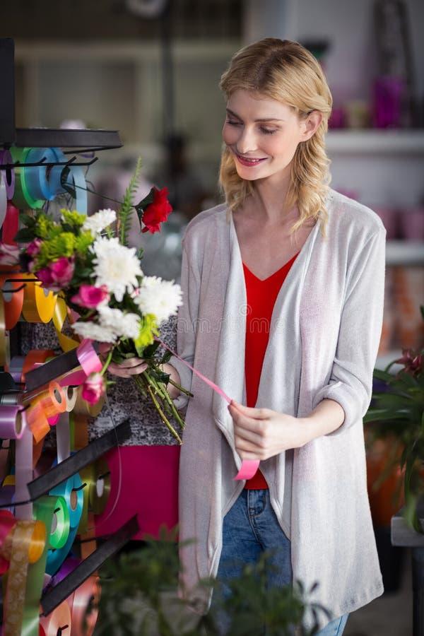 Kvinnlig blomsterhandlare som förbereder en blommabukett arkivfoto