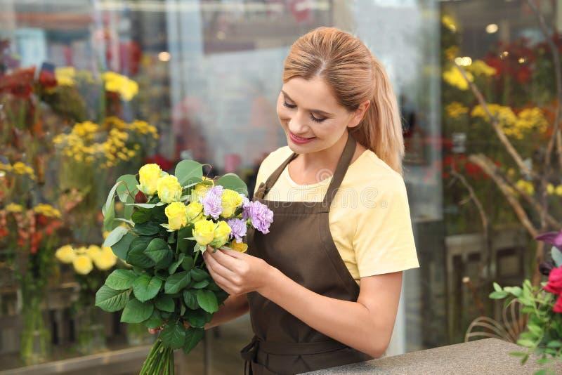 Kvinnlig blomsterhandlare som gör den härliga buketten i blomsterhandel royaltyfri bild