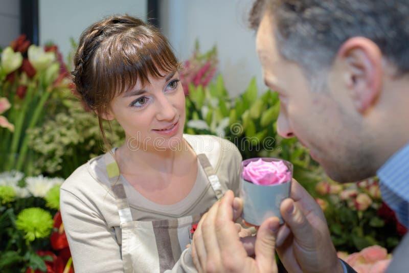 Kvinnlig blomsterhandlare som ger kundblomman till lukten royaltyfria foton