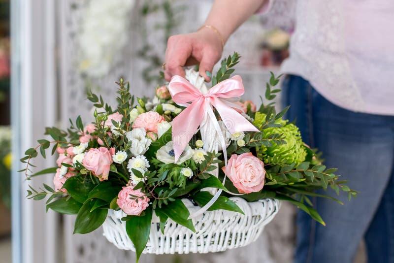 Kvinnlig blomsterhandlare som rymmer en härlig bukett av rosor i den vita korgen arkivfoto