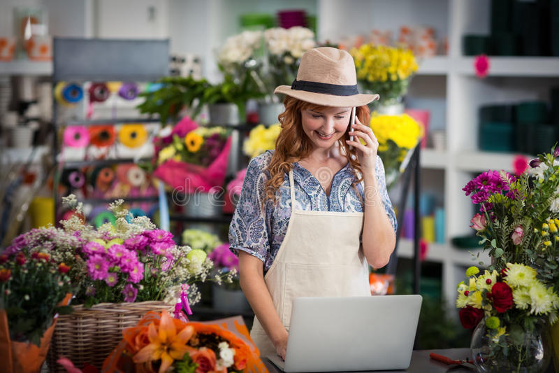 Kvinnlig blomsterhandlare som talar på mobiltelefonen, medan genom att använda bärbara datorn arkivbilder