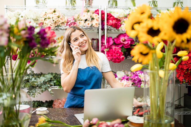 Kvinnlig blomsterhandlare som talar på telefonen arkivbilder