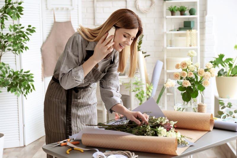 Kvinnlig blomsterhandlare som talar på telefonen, medan göra buketten arkivfoto