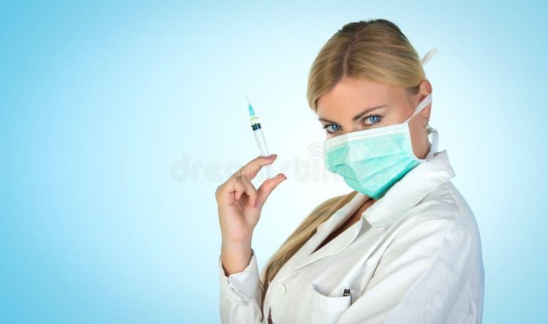 Kvinnlig blond doktor med den vaccinera injektionssprutan arkivbild