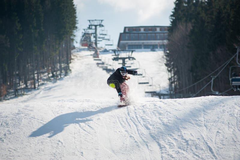 Kvinnlig boarder på snowboarden, når att ha hoppat över lutningen royaltyfri foto