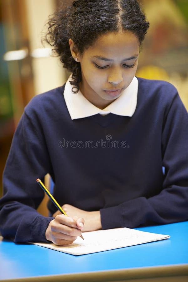 Kvinnlig bok för grundskolaelevhandstil i klassrum royaltyfria bilder