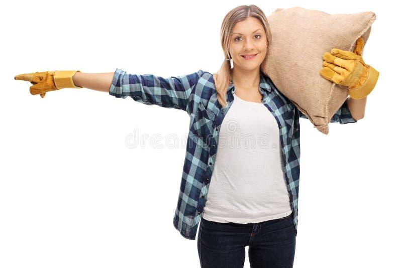 Kvinnlig bonde som bär en säck och peka royaltyfri fotografi