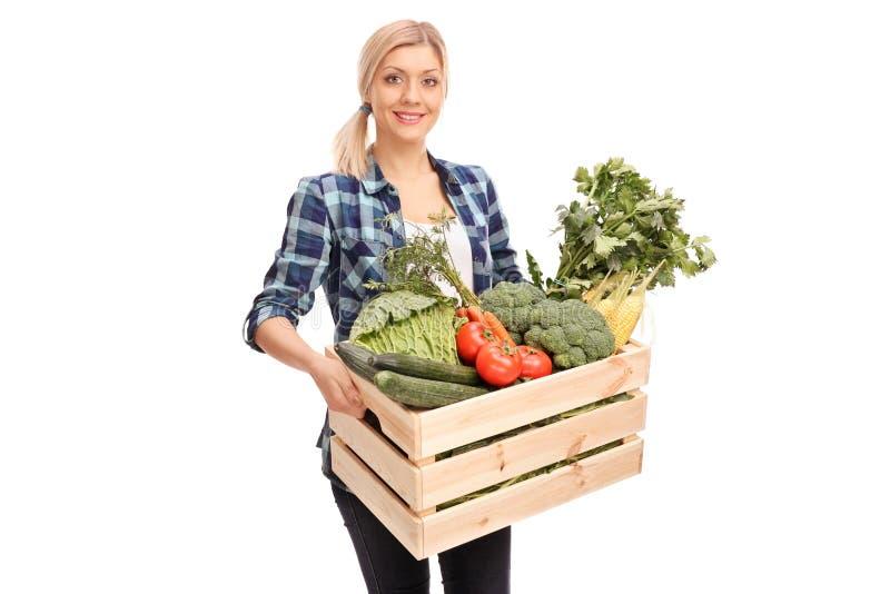 Kvinnlig bonde som bär en spjällåda med grönsaker royaltyfri foto