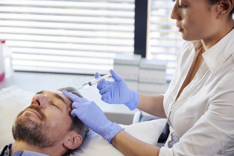 Kvinnlig Botox för kosmetologGiving Mature Male patient injektion i panna royaltyfria foton