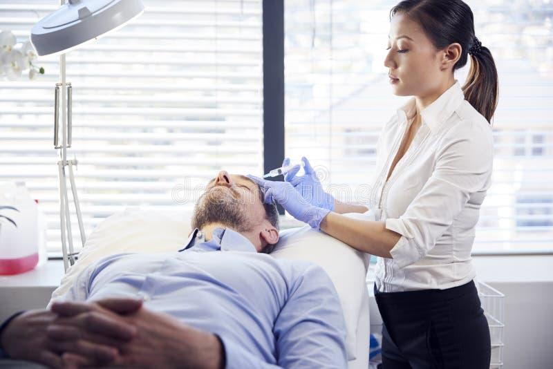 Kvinnlig Botox för kosmetologGiving Mature Male patient injektion i panna arkivbilder
