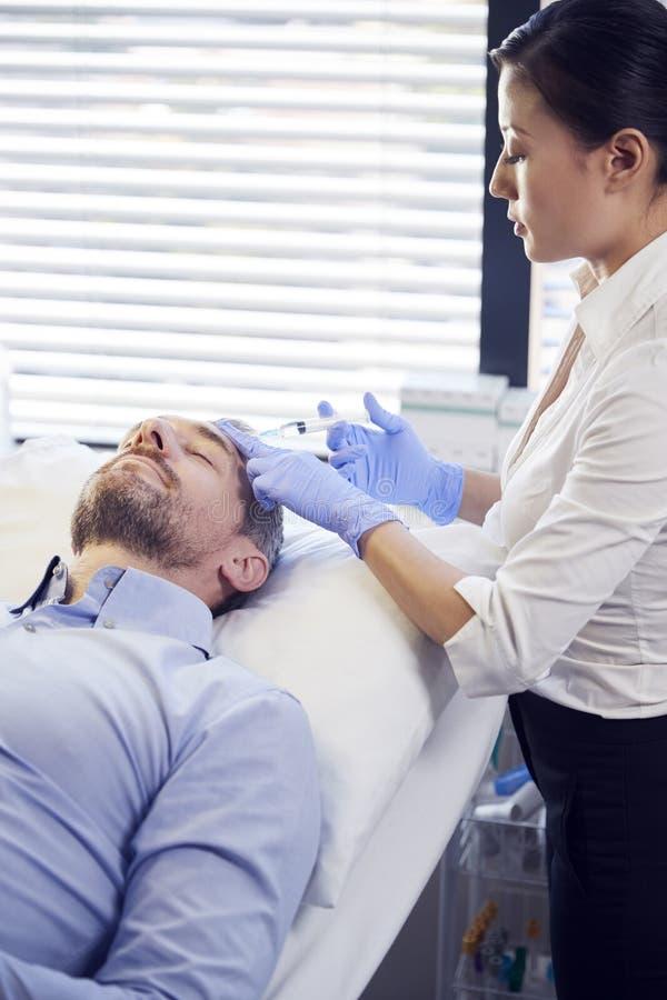 Kvinnlig Botox för kosmetologGiving Mature Male patient injektion i panna royaltyfri foto