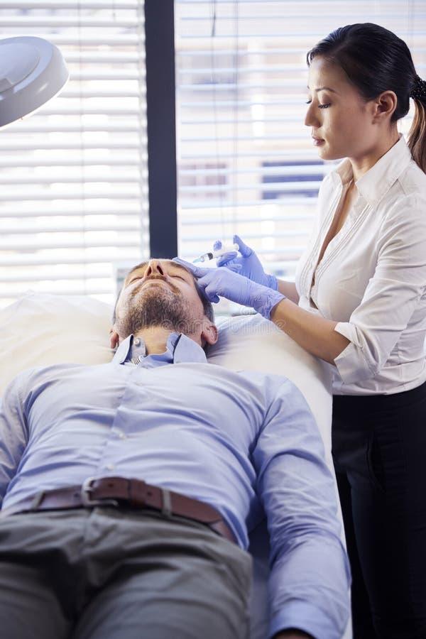 Kvinnlig Botox för kosmetologGiving Mature Male patient injektion i panna royaltyfria bilder