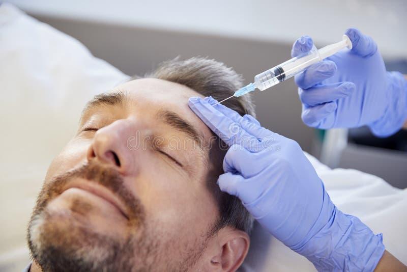 Kvinnlig Botox för kosmetologGiving Mature Male patient injektion i panna arkivbild