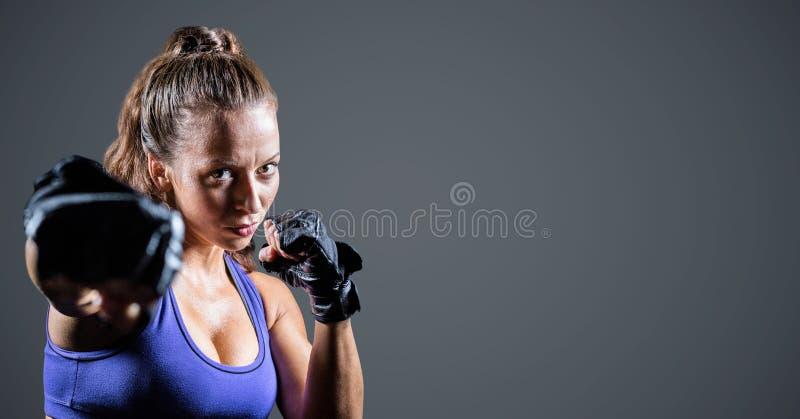 Kvinnlig boxare mot grå bakgrund royaltyfri fotografi