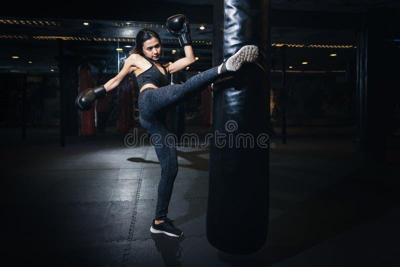 Kvinnlig boxare som slår en enorm stansa påse på en boxningstudio Wom royaltyfri fotografi