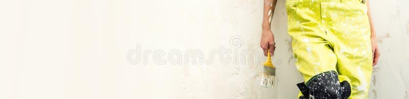 Kvinnlig byggmästare i borste för overallhållmålarfärg över panorama- bakgrund royaltyfria foton