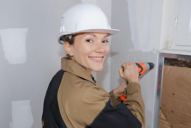 Kvinnlig byggmästare i overaller och hjälm med drillborren på vit royaltyfria bilder