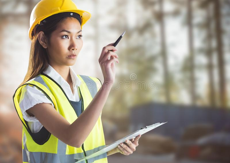 Kvinnlig byggmästare med skrivplattan mot oskarp byggnadsplats royaltyfria foton