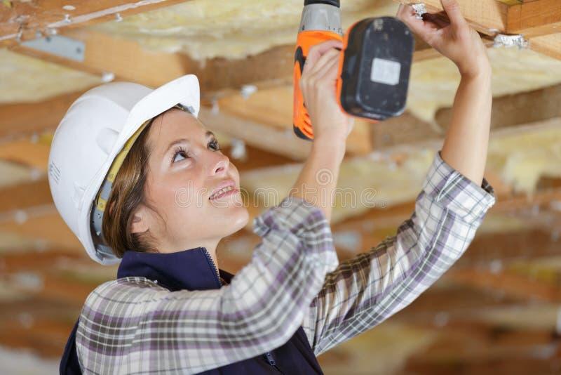 Kvinnlig byggmästare som använder den corless drillborren royaltyfria foton