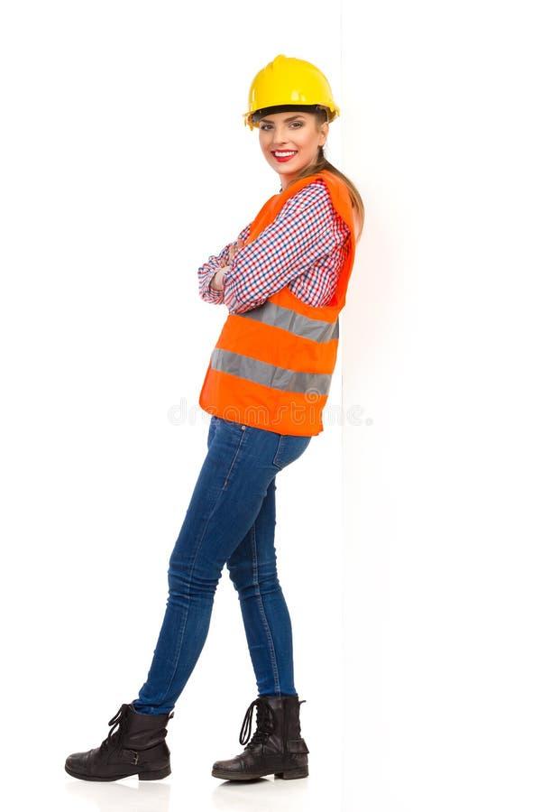 Kvinnlig byggnadsarbetare Leans On en vägg arkivfoton