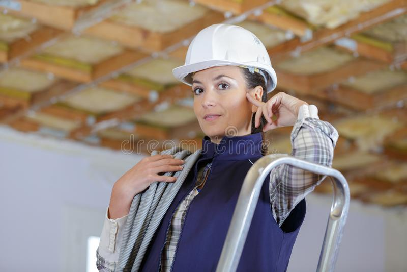 Kvinnlig byggnadsarbetare som lutar på stege i oavslutat rum royaltyfri foto