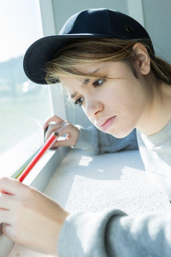 Kvinnlig byggnadsarbetare som sätter förseglingsskumbandet på fönster royaltyfri fotografi