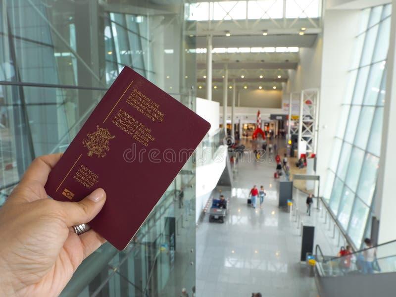 Kvinnlig caucasian hand som rymmer ett belgiskt pass i EU-terminalen i den Bryssel flygplatsen arkivbilder