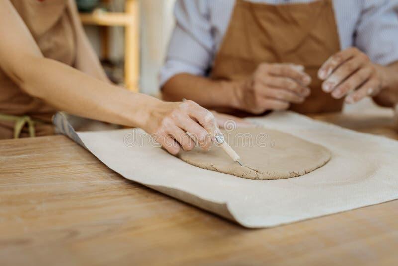 Kvinnlig ceramist som rymmer det funktionsdugliga hjälpmedlet, medan bilda vasen fotografering för bildbyråer