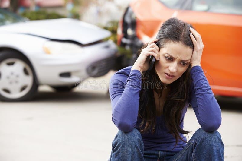 Kvinnlig chaufför Making Phone Call efter trafikolycka royaltyfri bild