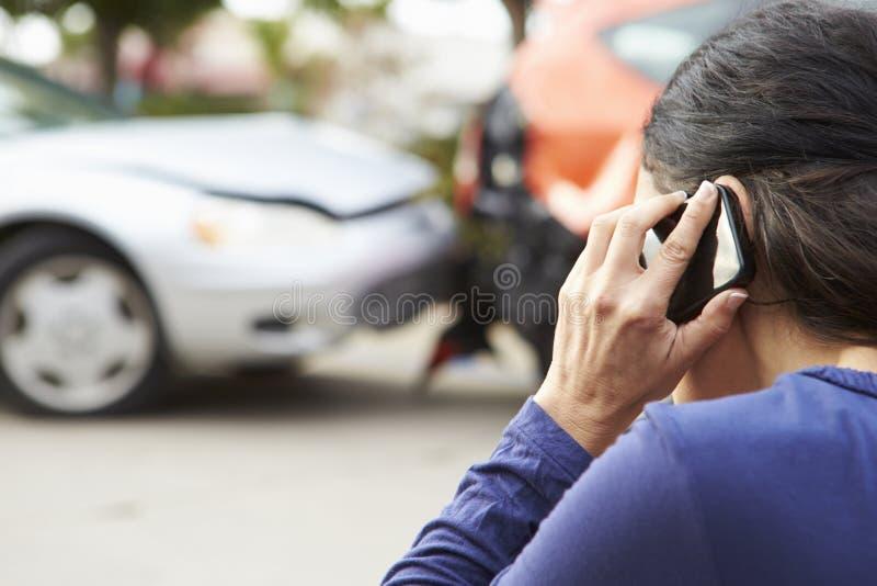Kvinnlig chaufför Making Phone Call efter trafikolycka arkivbild