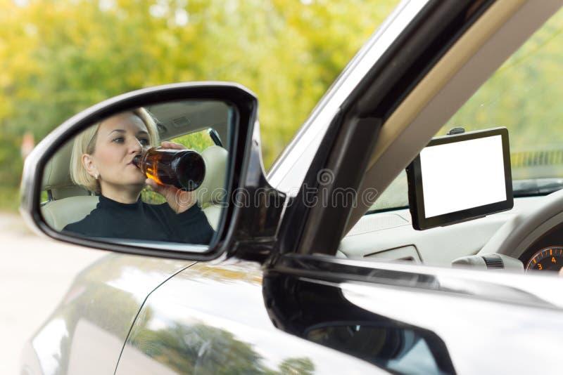 Kvinnlig chaufför som dricker, som hon kör royaltyfria bilder