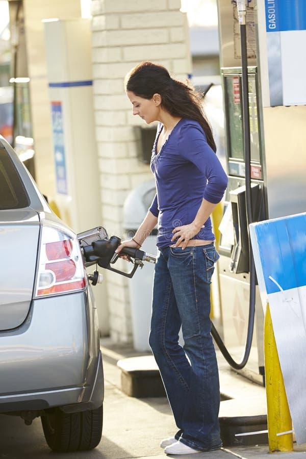Kvinnlig chaufförFilling Car At bensinstation arkivfoton